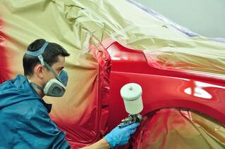 Spray Booth worker using an aerosol paint applicator.